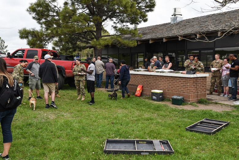 90th Missile Wing Airmen and their families enjoy a barbecue for the closing of Police Week, May 18, 2018, on F.E. Warren Air Force Base, Wyo. Police Week concluded with a festivities for Airmen and families to unwind after a week of events and work. In 1962, President John F. Kennedy signed a proclamation which designated May 15 as Peace Officers Memorial Day and the week in which that date falls as Police Week. People all across the United States participate in various events which honor those who have paid the ultimate sacrifice. (U.S. Air Force photo by Airman 1st Class Braydon Williams)
