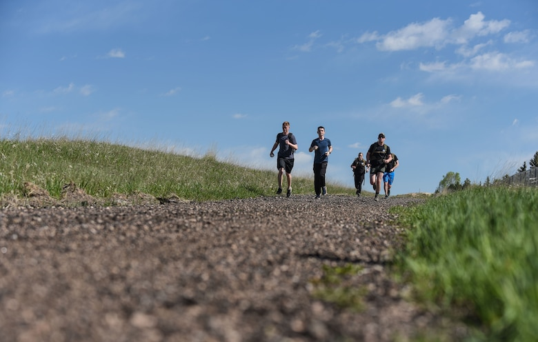 Airmen from the 90th Communications Squadron and 90th Security Forces Group approach the finish line of the six-mile run, walk or ruck for police week, May 17, 2018, on F.E. Warren Air Force Base, Wyo. The Police Week run, walk or ruck was a six-mile course around the northern perimeter of the base. Airmen could either participate or compete for fastest time. To place, their ruck had to weigh at least 35 pounds. In 1962, President John F. Kennedy signed a proclamation which designated May 15 as Peace Officers Memorial Day and the week in which that date falls as Police Week. People all across the United States participate in various events which honor those who have paid the ultimate sacrifice. (U.S. Air Force photo by Airman 1st Class Braydon Williams)