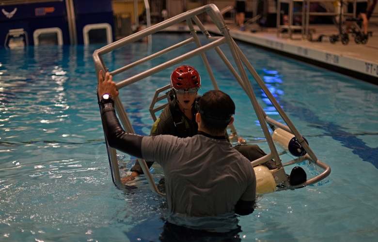 Nicole A. Mann, NASA astronaut, prepares to be flipped upside down by Survival Evasion Resistance and Escape specialists during a water survival course at Fairchild Air Force Base, Washington, May 18, 2018. One simulation that the NASA team completed during their stay at Fairchild, was the dunker course. Trainees are strapped inside a modular egress training system that simulates a mock helicopter with lap belts that submerges into water and rotates to teach aircrew how to find their exits to safety. (U.S. Air Force photo/Airman 1st Class Jesenia Landaverde)