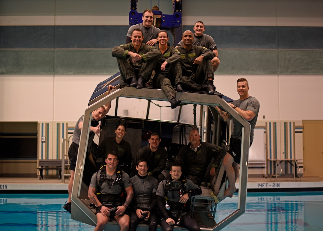 The NASA team and Survival, Evasion, Resistance and Escape specialist pose for a photo after completing the water survival course at Fairchild Air Force Base, Washington, May 18, 2018. The NASA team completed the dunker course. Trainees are strapped inside a modular egress training system that simulates a mock helicopter with lap belts that submerges into water and rotates to teach aircrew how to find their exits to safety. (U.S. Air Force photo/Airman 1st Class Jesenia Landaverde)