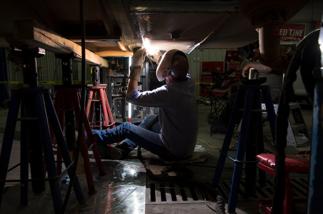 Mark Flannery, a welder from Detachment 6 at Al Udeid Air Base, Qatar, welds a steel plate to the bottom of a Jet Petroleum 8 tank in a vehicle management garage at an undisclosed location in Southwest Asia, April 27, 2018. Flannery was hand selected to come and repair the tank. (U.S. Air Force photo by Staff Sgt. Joshua King)