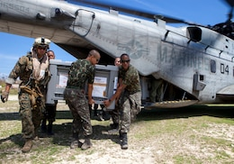 U.S. Marine Sgt. Jordan Becker, left, a cyber network specialist with Joint Task Force Matthew, offloads a generator from a CH-53E Super Stallion helicopter with the help of the Brazilian service members at Jeremie, Haiti, Oct. 15, 2016. After eight days of supply drop operations JTF Matthew has delivered over 478,000 pounds of supplies utilizing various military aircraft. JTF Matthew, a U.S. Southern Command-directed team comprised of Marines, soldiers, sailors and airmen, is providing critical airlift capabilities during the initial stages of the U.S. Agency for International Development's disaster relief operations in Haiti while the international response builds.