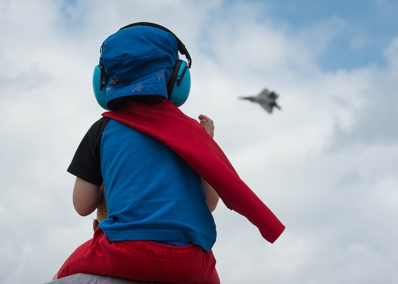 "A child watches U.S. Air Force Maj. Paul ""Loco"" Lopez, F-22 Raptor Demonstration Team commander and pilot, perform during the AirPower Over Hampton Roads JBLE Air and Space Expo at Joint Base Langley-Eustis, Virginia, May 20, 2018."