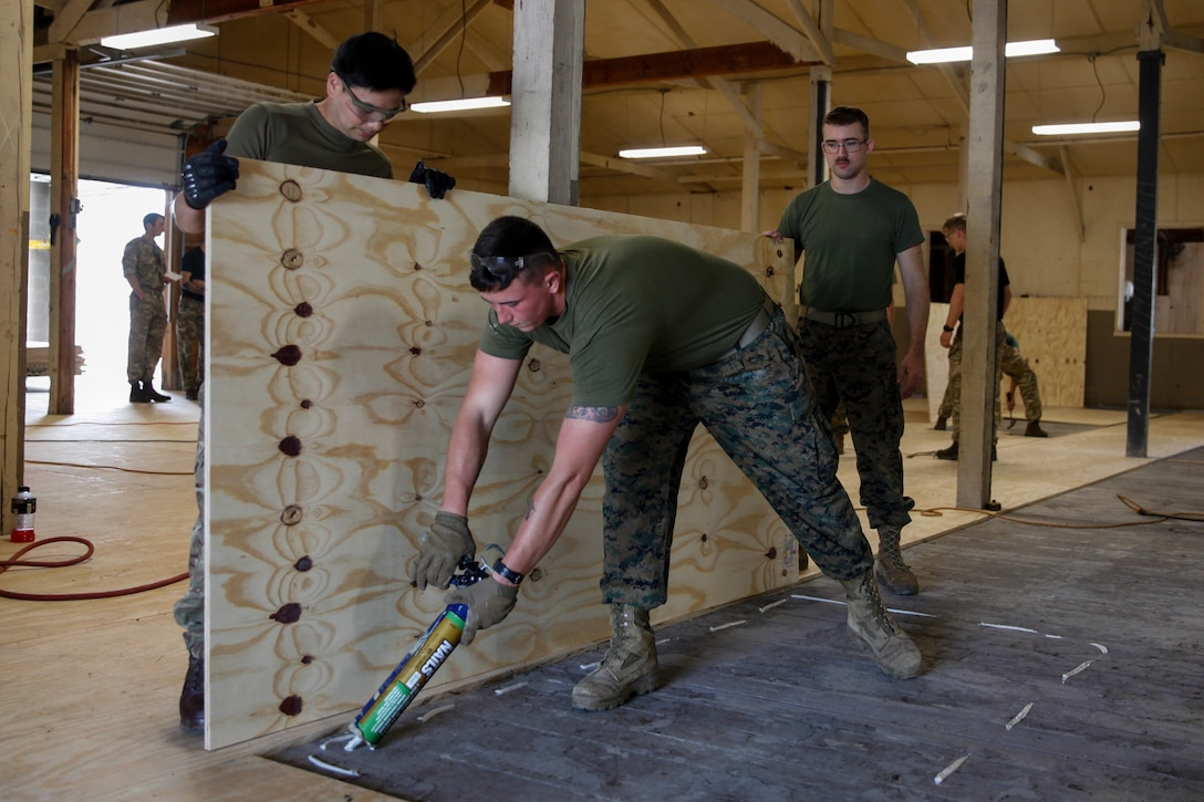U.S. Marine Lance Cpl. Wesley C. Blankenship, combat engineer with Bridge Company C, 6th Engineer Support Battalion, 4th Marine Logistics Group, uses liquid nail glue before putting down a piece of plywood at a construction site during exercise Red Dagger at Fort Indiantown Gap, Pa., May 21, 2018.