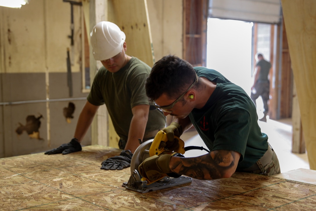 British Army Spr. Nathan Castle (right), commando with 131 Commando Squadron Royal Engineers, British Army, uses a circular saw to cut a piece of plywood while U.S. Marine Cpl. Junior G. Moncayo (left), heavy equipment mechanic with Bridge Company B, 6th Engineer Support Battalion, 4th Marine Logistics Group, holds the wood in place at a construction site during exercise Red Dagger at Fort Indiantown Gap, Pa., May 21, 2018.