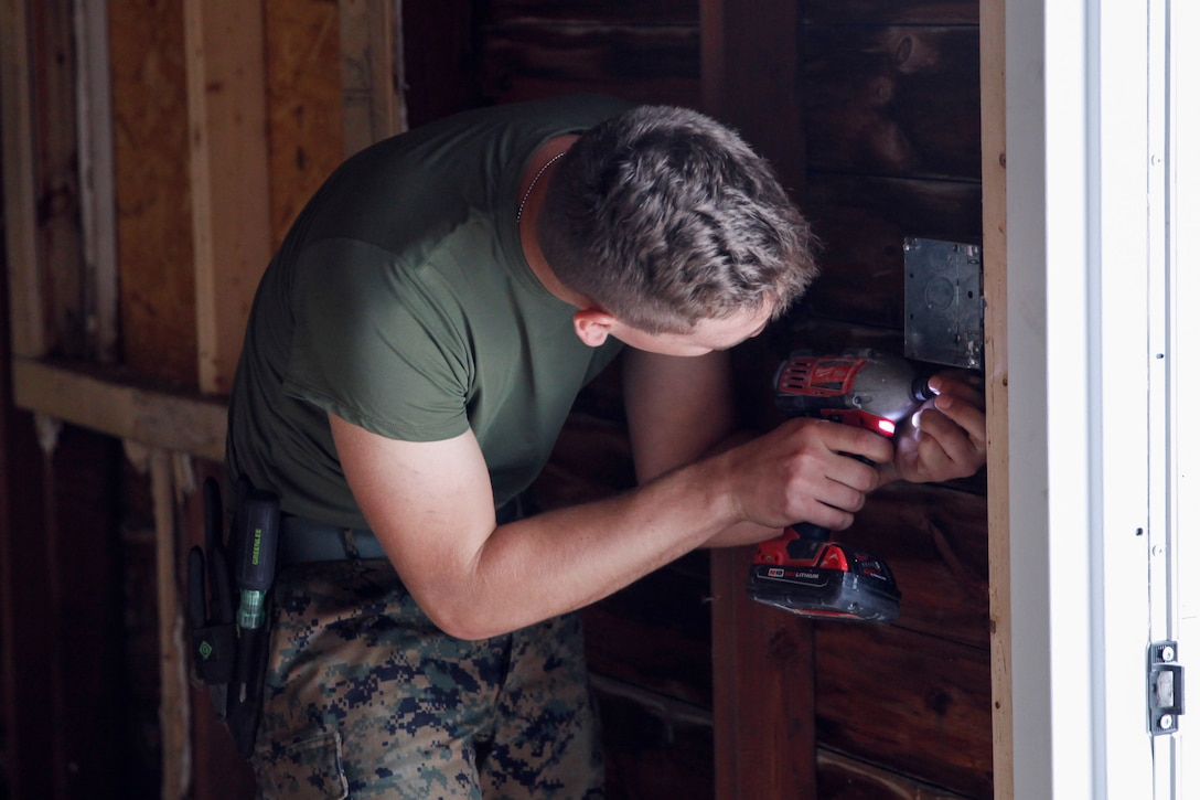 U.S. Marine Lance Cpl. Blake A. Schult, motor vehicle mechanic with Engineer Company C, 6th Engineer Support Battalion, 4th Marine Logistics Group, drills a screw into an outlet at a construction site during exercise Red Dagger at Fort Indiantown Gap, Pa., May 21, 2018.