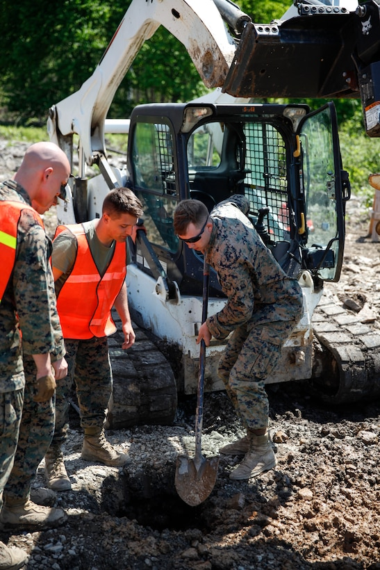 U.S. Marine Lance Cpl. Mitchell R. Neimann (left), heavy equipment operator with Engineer Company C, 6th Engineer Support Battalion, 4th Marine Logistics Group, digs a hole at a construction site during exercise Red Dagger at Fort Indiantown Gap, Pa., May 21, 2018.