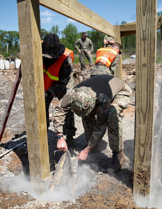 U.S. Marines with 6th Engineer Support Battalion, 4th Marine Logistics Group, and British commando's with 131 Commando Squadron Royal Engineers, British Army, pour cement into holes to fill in the wooden framework at a construction site during exercise Red Dagger at Fort Indiantown Gap, Pa., May 21, 2018.