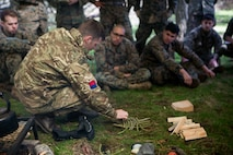 British Army Staff Sgt. Steven Kelly, survival instructor with 29th Commando Regiment, Artillery Battery, shows Marines with 4th Air Naval Gunfire Liaison Company, Force Headquarters Group, how to properly set a fire with wood found in the wilderness, in Durness, Scotland, April 26, 2018.