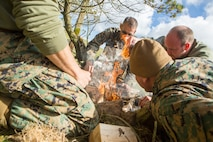 British Army Medical Assistant Jim Collier (right), 29th Commando Regiment, Royal Artillery, shows Marines and sailors with 4th Air Naval Gunfire Liaison Company, Force Headquarters Group, how to properly start a fire during survival training, in Durness, Scotland, April 26, 2018.