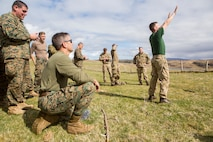 While conducting survival training, British Army Staff Sgt. Steven Kelly (right), survival instructor with 29th Commando Regiment, Artillery Battery, teaches Marines with 4th Air Naval Gunfire Liaison Company, Force Headquarters Group, how to properly tell direction by the placement of hands in the sky, in Durness, Scotland, April 26, 2018.