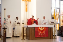 Members of the U.S.military chapel leadership stand for the reading of the Bible during the final Catholic mass at RAF Mildenhall, England, May 14, 2018. The Catholic Parish falls under Our Lady of Walsingham Catholic Community, and has been a part of RAF Mildenhall since 1955. (U.S. Air Force photo by Airman 1st Class Alexandria Lee)