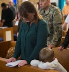 A mother and her son bow their heads in prayer during the final Catholic mass at RAF Mildenhall, England, May 14, 2018. The Catholic Parish falls under Our Lady of Walsingham Catholic Community, and has been a part of RAF Mildenhall since 1955. (U.S. Air Force photo by Airman 1st Class Alexandria Lee)
