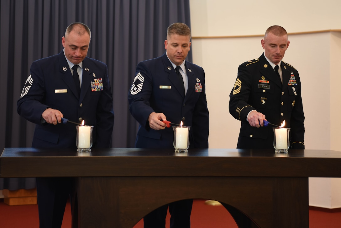 Members of the Ramstein Area Chief's Group light candles during Kindergraves Memorial at Daenner Kaserne Chapel in Kaiserslautern, Germany, May 19, 2018. The Chief's group is one of the organizations responsible for the up-keep of the gravesite.