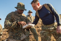 U.S. Marine Corps Lance Cpl. Gregory McDonald (left), a radio operator with 4th Air Naval Gunfire Liaison Company, Force Headquarters Group, and Royal Navy Chief Petty Officer Andrew Douglas (right), a Royal Navy coordinator with 148 Commando Battery, 29th Commando Royal Artillery, discuss route options for a checkpoint during a land navigation exercise in Durness, Scotland, April 30, 2018.