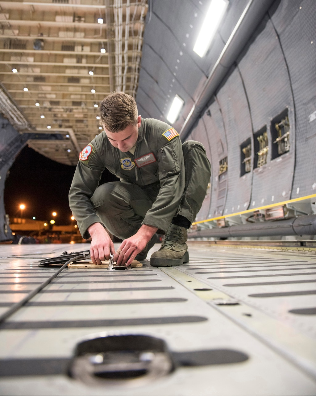 U.S. Air Force Senior Airman Robert Harold, loadmaster with the 22nd Airlift Squadron, Travis Air Force Base, Calif., secures a pulley on a C-5M Super Galaxy.