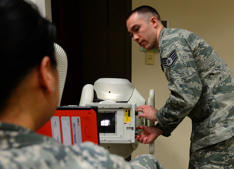 "Staff Sgt. Ryan Gulland, a 28th Medical Support Squadron diagnostic imaging technician, captures a ""sunrise"" X-ray image of Master Sgt. Mia Newmeyer, 28th MDSS diagnostic imaging noncommissioned officer in charge, inside the 28th Medical Group at Ellsworth Air Force Base, S.D., May 11, 2018. This X-ray image is captured by positioning the patient with the knees slightly bent and an x-ray cassette placed behind the knee being examined, so the produced image gives the appearance of a sunrise. (U.S. Air Force photo by Senior Airman Denise Jenson)"