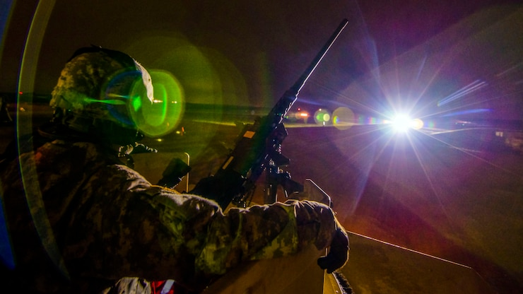 A soldier, shown in profile, sits in a turret at night by a machine gun, illuminated by flashes of light.