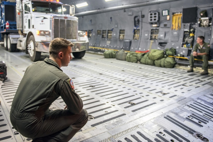 Airmen watch as a large truck is loaded onto an aircraft.