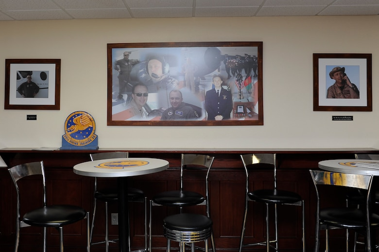 Photos of Maj. Jeff 'Oz' Ausborn fill a wall within the memorial heritage room at the 99th Flying Training Squadron at Joint Base San Antonio-Randolph, Texas, April 27, 2018. Ausborn was deployed from JBSA-Randolph and killed April 27, 2011, in Kabul, Afghanistan, when a shooter opened fire at the Kabul International Airport, killing eight Airmen and one American contractor. (U.S. Air Force photo by Tech. Sgt. Ave I. Young)