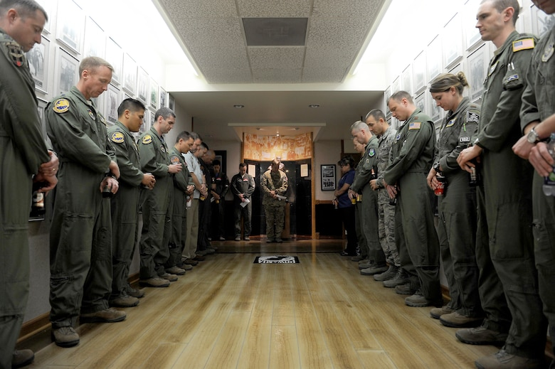Members of the 99th Flying Training Squadron line Freedom Flyer hallway of Hangar 12 during a roll call for the NATO Air Training Command Afghanistan, NATC-A NINE, April 27, 2018, Randolph AFB, Texas. On this day in 2011 a shooter opened fire at the Kabul International Airport, killing eight Airmen and one American contractor. Among the victims was Maj. Jeff 'Oz' Ausborn, who was deployed from the 99th FTS. (U.S. Air Force photo by Tech. Sgt. Ave I. Young)