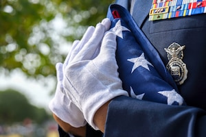An airman's white-gloved hands hold a U.S. flag folded into a triangle against his chest.