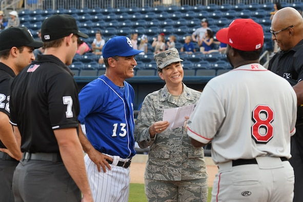 Col. Debra A. Lovette, 81st Training Wing commander, joins Mike Guerrero, Biloxi Shuckers manager, at home plate to meet with the umpires and the opposing team's manager during a Biloxi Shuckers baseball game, in Biloxi, Mississippi, May 17, 2018. Lovette also threw the first pitch during pre-game festivities. (U.S. Air Force photo by Kemberly Groue)