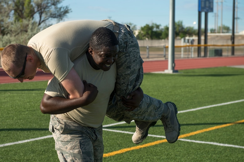 Airman 1st Class Anthony Ford and Senior Airman Steven Waller, 366th Security Forces Squadron response force members, perform a fireman's carry during the National Police Week memorial workout, May 15, 2018, at Mountain Home Air Force Base, Idaho. The memorial workout included 14 workouts and 14 repetitions to honor the fallen defenders. (U.S. Air Force Photo by Airman 1st Class JaNae Capuno)