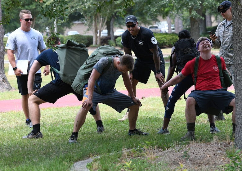 Members of the 81st Communications Squadron team participate in partner squats during the 81st Security Forces Squadron 5K Fallen Defender Ruck and Obstacle Course competition at the Crotwell Track at Keesler Air Force Base, Mississippi, May 15, 2018. The event was held during National Police Week, which recognizes the service of law enforcement men and women who put their lives at risk every day. (U.S. Air Force photo by Kemberly Groue)