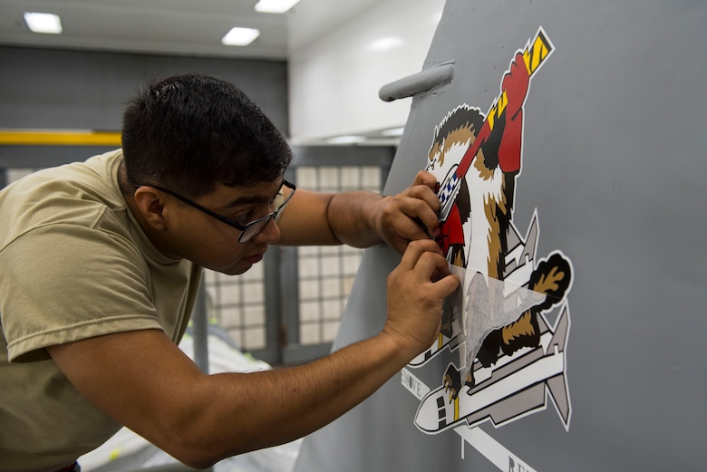 U.S. Air Force Senior Airman Israel Marrufo, 20th Equipment Maintenance Squadron corrosion control specialist, peels paper off a Wild Weasel decal at Shaw Air Force Base, S.C., May 16, 2018.