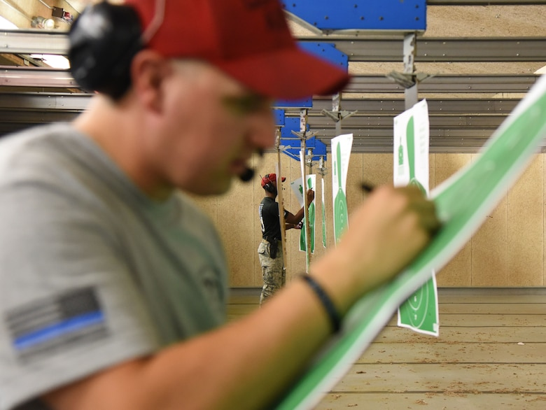 U.S. Air Force Staff Sgt. Derek Gioia, left, and Thane Sandy, 81st Security Forces Squadron combat arms instructors, calculates target scores during the 81st SFS law enforcement team competition shoot in the indoor firing range at Keesler Air Force Base, Mississippi, May 16, 2018. The event was held during National Police Week, which recognizes the service of law enforcement men and women who put their lives at risk every day. (U.S. Air Force photo by Kemberly Groue)