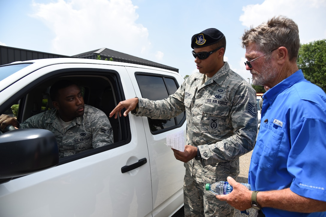 U.S. Air Force Tech. Sgt. Anthony Horton, 81st Security Forces Squadron flight chief, and Airman 1st Class Keshaun Survine, 81st SFS base defense operations center controller, provide a traffic violation demonstration for Brad Bordes, grandfather of Airman Noah Hill, 81st SFS entry controller, during the 81st SFS open house at Keesler Air Force Base, Mississippi, May 17, 2018. The open house allowed individuals to walk through a day in the life of a defender. The event was held during National Police Week, which recognizes the service of law enforcement men and women who put their lives at risk every day. (U.S. Air Force photo by Kemberly Groue)