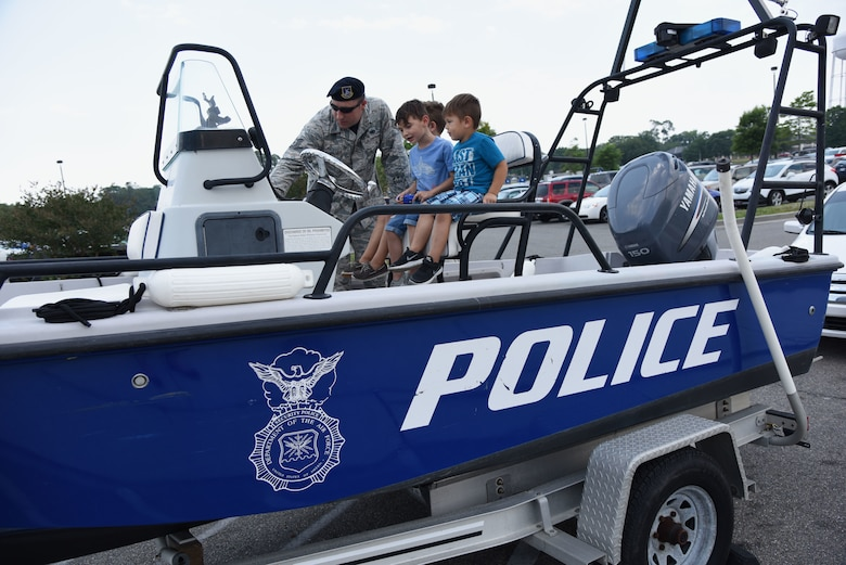 U.S. Air Force Tech. Sgt. Jared Miller, 81st Security Forces Squadron unit deployment manager, gives a tour of the 81st SFS patrol boat to kids during the 81st SFS fun day at the base exchange at Keesler Air Force Base, Mississippi, May 18, 2018. Fun day allowed individuals to view a military working dog demonstration, a combat arms weapons stand as well as tour SFS vehicles and equipment. The event was held during National Police Week, which recognizes the service of law enforcement men and women who put their lives at risk every day. (U.S. Air Force photo by Kemberly Groue)