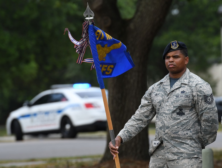 U.S. Air Force Tech. Sgt. Courtney Hill, 81st Security Forces Squadron commander support staff NCO in charge, holds the 81st SFS guidon during the 81st SFS retreat ceremony at Keesler Air Force Base, Mississippi, May 18, 2018. The event was held during National Police Week, which recognizes the service of law enforcement men and women who put their lives at risk every day. (U.S. Air Force photo by Kemberly Groue)