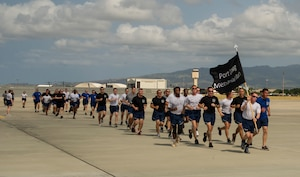 Airmen from 515th Air Mobility Operations Wing run in formation during the 5th Annual Port Dawg Memorial Run at Joint Base Pearl Harbor-Hickam, Hawaii, May 18, 2018. The purpose of the run was to honor and remember fallen Port Dawgs, Airmen who lost their lives in the air transportation career field. (Photo by Tech. Sgt. Heather Redman)