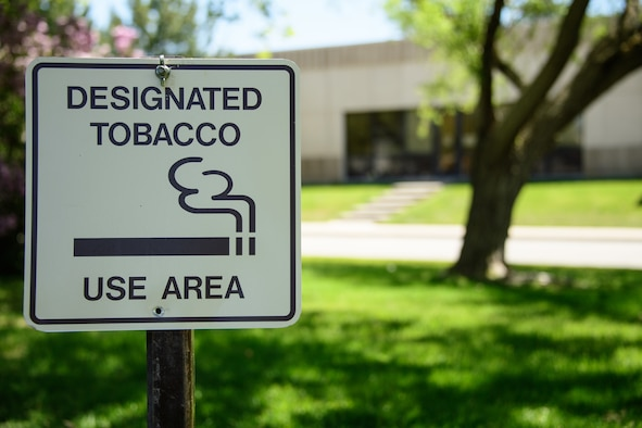 A sign marks the newly designated tobacco use area for the Hill medical campus, May 8, 2018, Hill Air Force Base, Utah. All tobacco use areas were removed from the campus April 27, 2018. The only tobacco use area for visitors and occupants of the campus in located north and across the street from the base clinic, building 570. (U.S. Air Force photo by R. Nial Bradshaw)