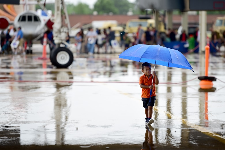 A child walks with umbrella in hand toward the MQ-9 Reaper at Joint Base Langley-Eustis, Virginia, May 19, 2018. The MQ-9 Display gathered the attention of aviation enthusiasts of all ages over the weekend for the Airpower Over Hampton Roads air show. (U.S. Air Force photo by Airman 1st Class Haley Stevens)