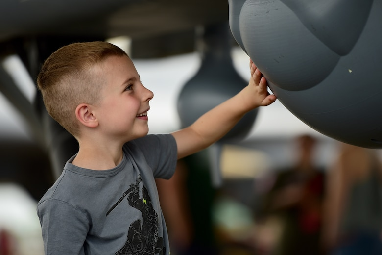 A child gets an up-close view of the MQ-9 Reaper at Joint Base Langley-Eustis, Virginia, May 19, 2018. This was the first time the MQ-9 Reaper was displayed during an air show at the Air Combat Command headquarters. (U.S. Air Force photo by Airman 1st Class Haley Stevens)