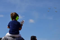 A child watches the U.S. Air Force Thunderbirds air demonstration team perform during the Airpower Over Hampton Roads air show at Joint Base Langley-Eustis, Virginia, May 20, 2018. This performance marked the first Thunderbirds demonstration since the start of this air show season. (U.S. Air Force photo by Airman 1st Class Haley Stevens)