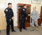 """From right to left: Brig. Gen. Carl Schaefer, 412th Test Wing commander, presents Officers Randy Plata and Miguel Madrid test wing coins May 22 to thank them for actions they took during a """"gate runner"""" incident in April. (U.S. Air Force photo by Kenji Thuloweit)"""
