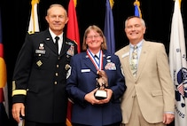 Master Sgt. Jeanette Rummel, a 731st Airlift Squadron evaluator flight engineer, poses for a photo with U.S. Army Maj. Gen. Randy George, the 4th Infantry Division commander, left, and Mark Seglem, the regional vice president of Colorado Campuses, right, during the 2018 Armed Forces Luncheon, in Colorado Springs, Colorado, May 17, 2018.