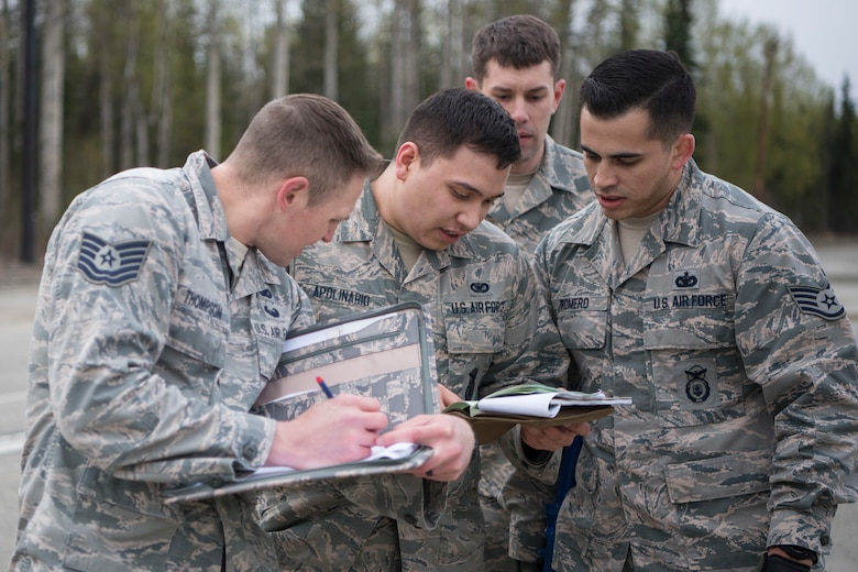 Air Force Tech. Sgt. Michael Thompson, 673d Security Forces Squadron operations support noncommissioned officer in charge, assesses a team's reading of a 9-line MEDEVAC call, at the Defenders Day Challenge on Joint Base Elmendorf-Richardson, Alaska, May 16, 2018. The 9-line MEDEVAC call consists of stating information such as location, patient status, security, radio frequency and more.