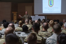 Airman briefs room filled with people