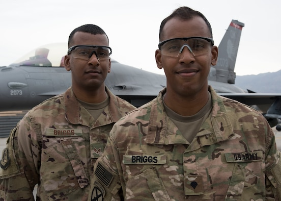Senior Airman Elliot Briggs (left), a maintenance analyst technician with the 455th Expeditionary Maintenance Group, and Spc. Leon Briggs, a vehicle mechanic with the 1-87th Infantry Battalion, 10th Mountain Infantry Division, pose for a photo at Bagram Airfield, Afghanistan, May 12. The deployment to Afghanistan is the first time the two brothers have been deployed to the same location since enlisting. (U.S. Air Force photo/Tech. Sgt. Eugene Crist)