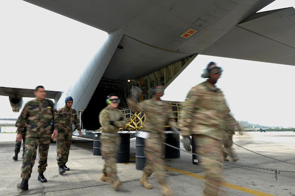 Royal Moroccan Armed Forces service members and 435th Contingency Response Group Airmen walk away from a Super Hercules C130-J during a combat offload training for Exercise African Lion 18, April 23, 2018 at Kenitra Air Base, Morocco.