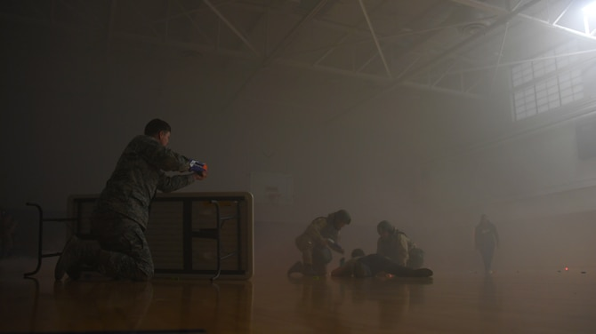 Staff Sgt. Jacob Williams, unit deployment manager with the 319th Logistics Readiness Squadron, left, simulates a combat environment by firing foam darts towards team members of the 319 LRS as they provide self-aid and buddy care during a readiness competition May 18, 2018, on Grand Forks Air Force Base, North Dakota. The readiness competition consisted of 10 stations meant to test Airmen on their knowledge and application of SABC, chemical, biological, radiological and nuclear weapon safety, map-reading, hand-to-hand combat, weapons assembly and more. (U.S. Air Force photo by Airman 1st Class Elora J. Martinez)