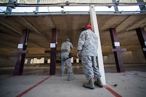 CATM Airman helps Airman shoot pistol during competition