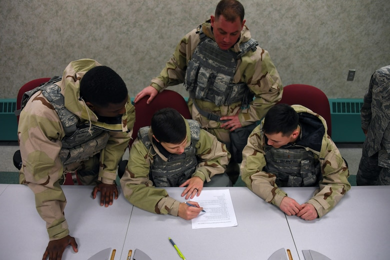 Members of the 319th Security Forces Squadron work together during a readiness competition to complete a written test on chemical, biological, radiological and nuclear weapons May 18, 2018, on Grand Forks Air Force Base, North Dakota. Units across the base created teams of Airmen to participate in the competition, testing their knowledge and application of topics to include CBRN, self-aid and buddy care, weapons assembly, hand-to-hand combat and map-reading. (U.S. Air Force photo by Airman 1st Class Elora J. Martinez)