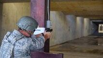 Airmen fires M9 pistol at silhouette target.