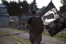 Airman walks during ruck march holding POW/MIA flag